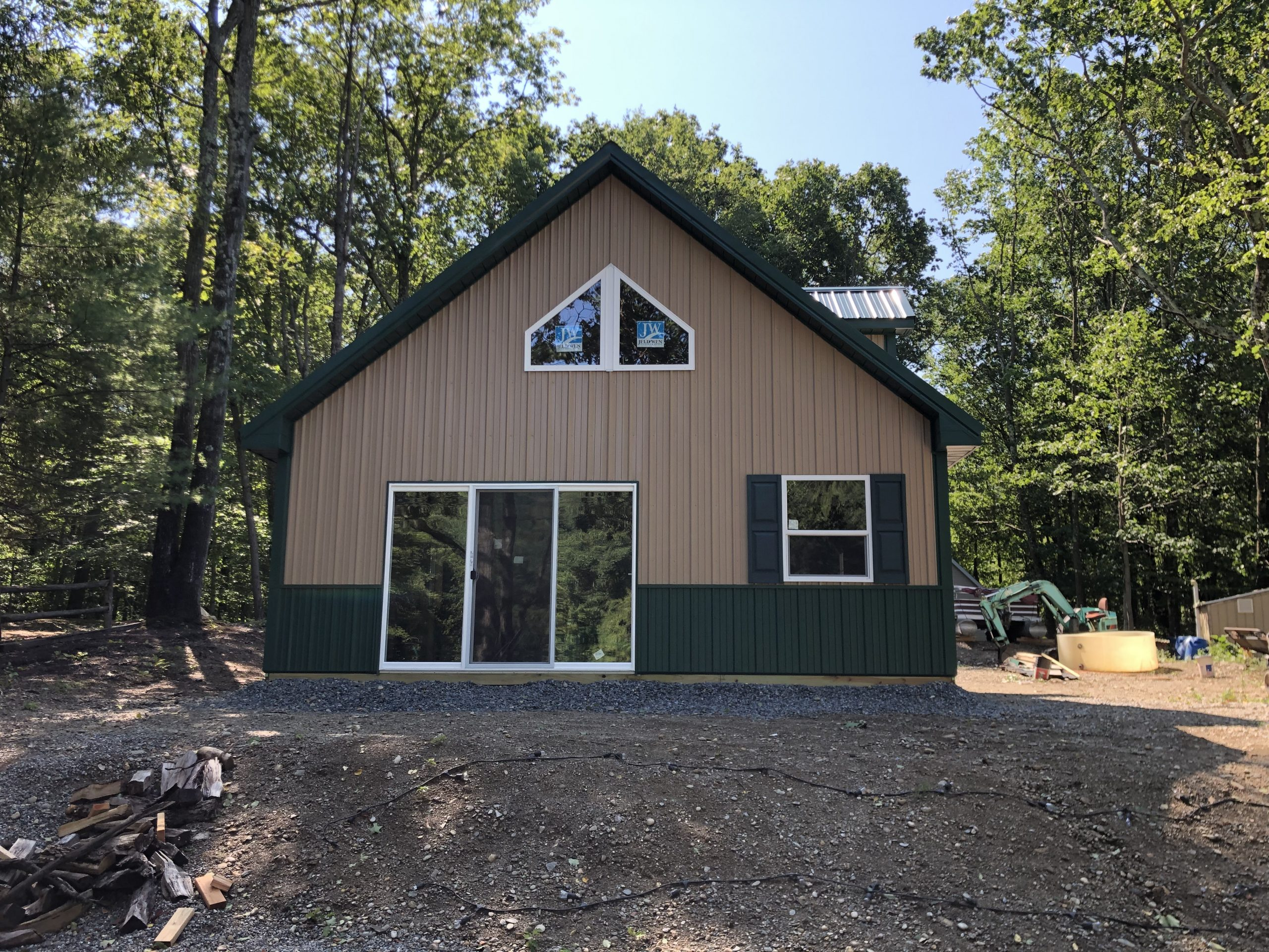 green and tan new pole barn home