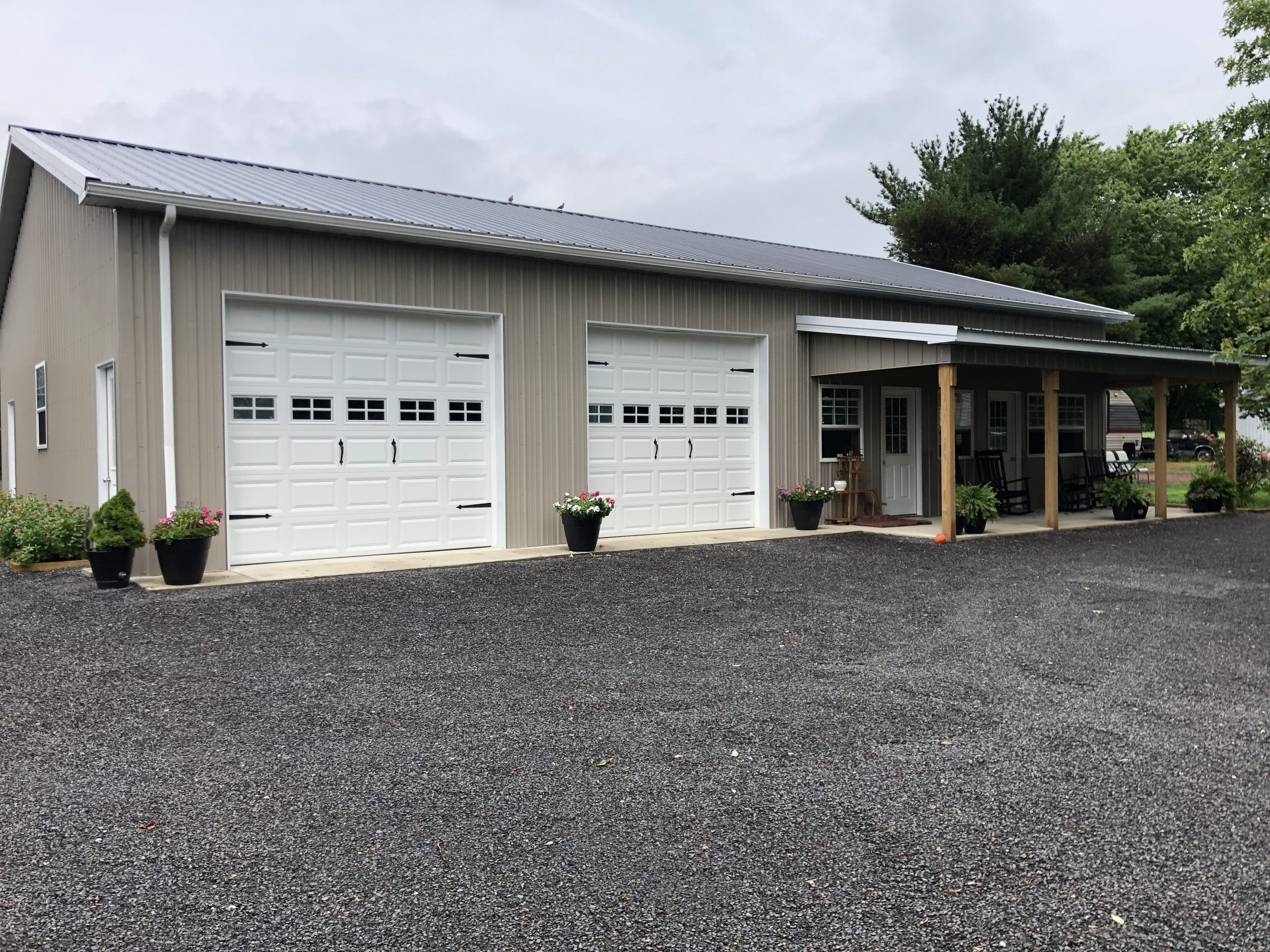 tan metal pole garage with small attached porch
